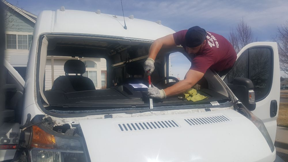 Glass expert works on removing a shattered windshield for replacement